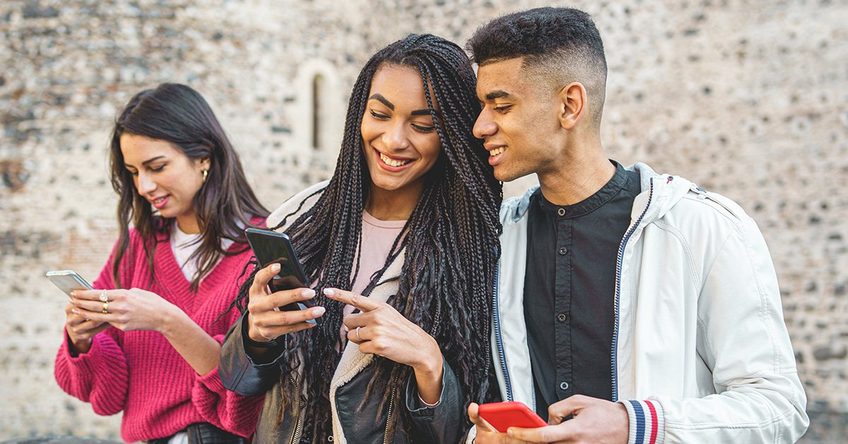 young diverse students on cell phone