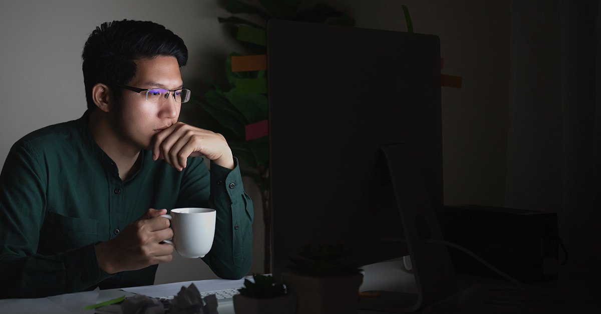 man sitting at computer with coffee thinking