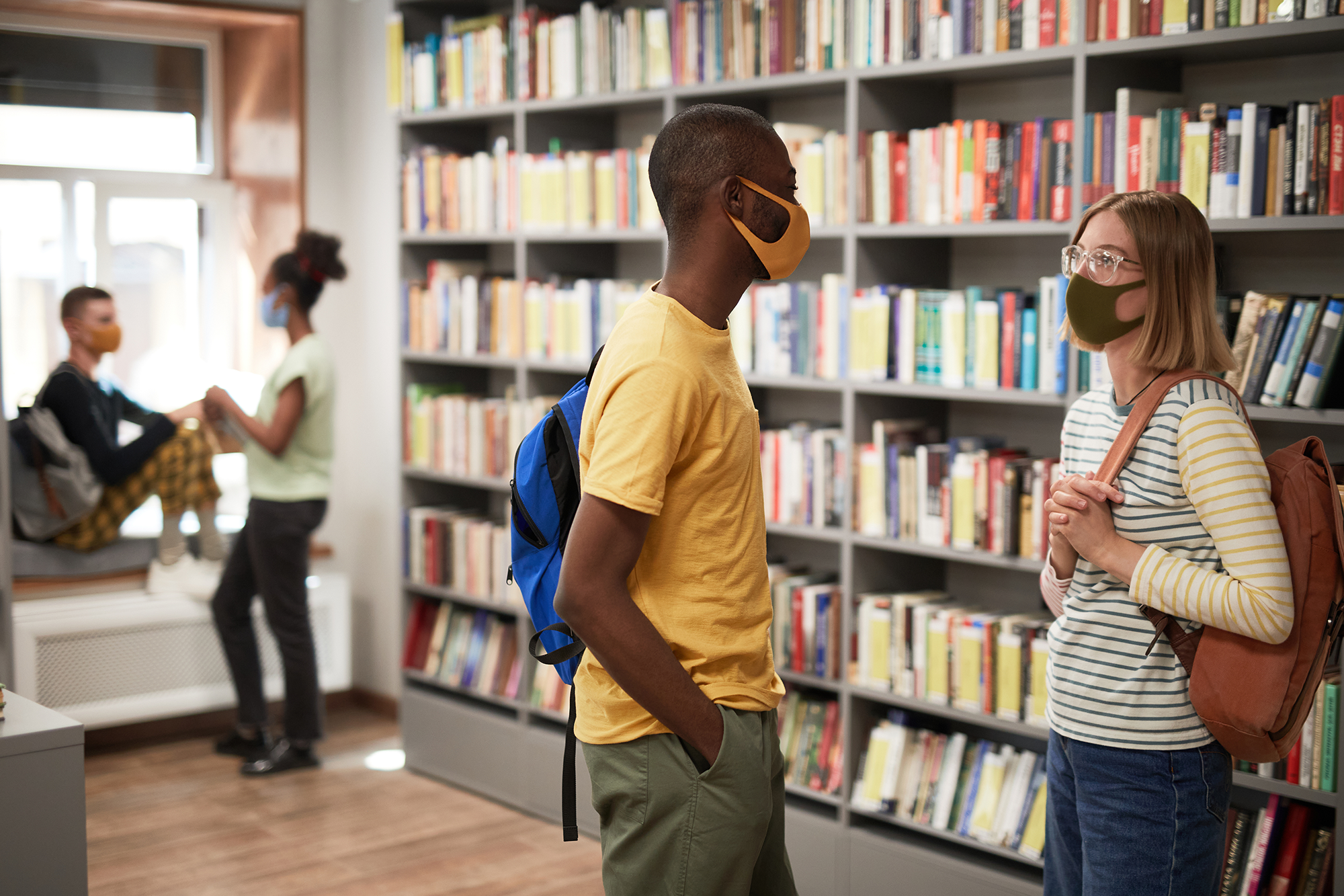 masked students talking in library