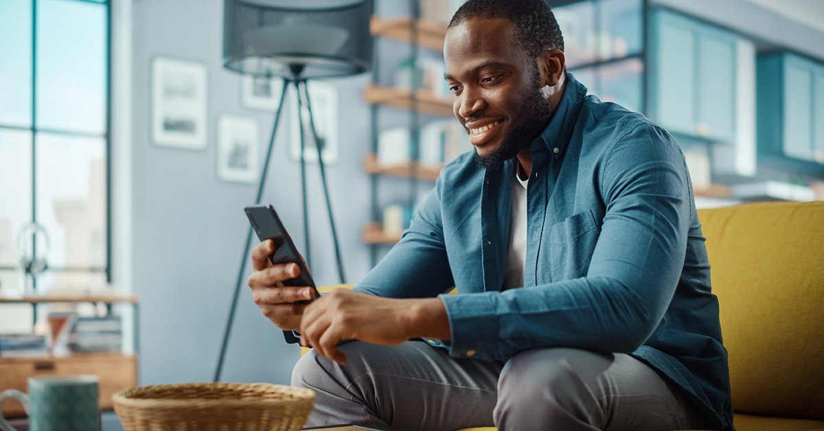 man looking at cell phone in living room